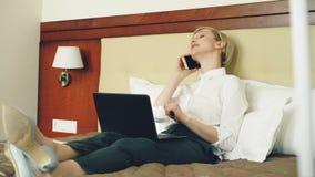 Mulher de negócios de sorriso na camisa branca usando-se no portátil e falando no telefone celular ao encontrar-se na cama na sal video estoque