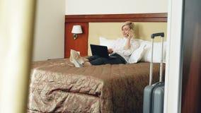 Mulher de negócios de sorriso na camisa branca usando-se no portátil e falando no telefone celular ao encontrar-se na cama na sal vídeos de arquivo