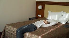 Mulher de negócios de sorriso que cai e que encontra-se na cama relaxado na sala de hotel Curso, negócio e conceito dos povos filme