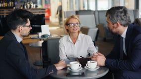 Mulher de negócios de sorriso que discute o trabalho com os sócios masculinos durante o encontro no café video estoque