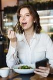 Mulher de negócios de sorriso que tem o lucnch no café dentro fotos de stock royalty free