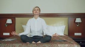 Mulher de negócios de sorriso que toma o assento da posição de lótus da ioga relaxado na cama na sala de hotel Curso, negócio e p filme