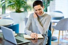 Mulher de negócios de sorriso Speaking pelo telefone com cliente imagens de stock royalty free