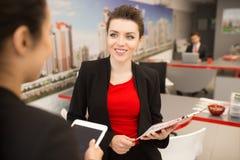 Mulher de negócios de sorriso Talking ao colega foto de stock