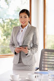 Mulher de negócios Standing In Boardroom com tabuleta de Digitas Foto de Stock