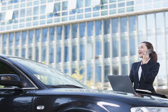 Mulher de negócios Standing pelo carro no telefone Imagens de Stock