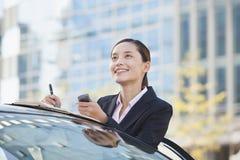 Mulher de negócios Standing pelo carro usando o telefone e tomando notas Fotos de Stock Royalty Free