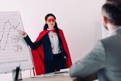 mulher de negócios super na máscara e cabo que mostra a apresentação para o homem de negócios imagem de stock royalty free