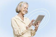 Mulher de negócios superior feliz que usa o PC da tabuleta contra o céu azul claro Fotografia de Stock Royalty Free