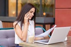 A mulher de negócios tem a conversação telefônica, documentação do negócio dos estudos, análise financeira, senta-se na frente do imagens de stock royalty free