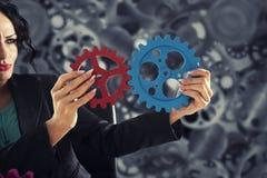 A mulher de negócios tenta conectar partes das engrenagens Conceito dos trabalhos de equipe, da parceria e da integração fotografia de stock