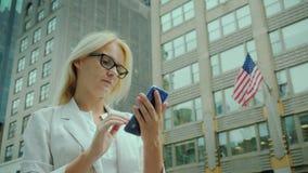 A mulher de negócios usa o smartphone na rua de New York no fundo do prédio de escritórios com a bandeira americana vídeos de arquivo