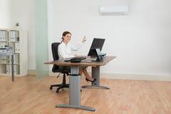 Mulher de negócios Using Air Conditioner no escritório Imagem de Stock