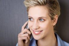 Mulher de negócios Using Mobile Phone ao olhar afastado contra a parede foto de stock