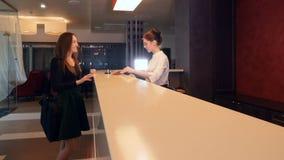 A mulher de negócios vem ao hotel, verificando dentro em uma mesa de recepção 4K video estoque