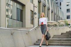 Mulher de negócios Walking On Street e guardar o café quente Foto de Stock Royalty Free