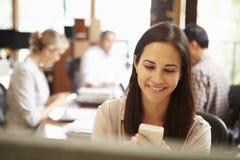 Mulher de negócios Working At Desk que usa o telefone celular Imagens de Stock