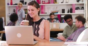 Mulher de negócios Working On Laptop no escritório ocupado video estoque