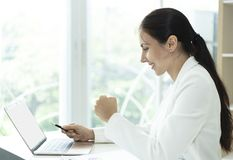 Mulher de neg?cio feliz que olha o computador com bra?os acima successful imagens de stock royalty free