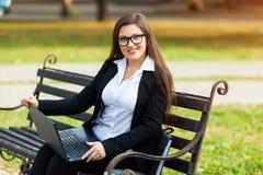 Mulher de neg?cio que senta-se no parque em um banco, trabalhando com um port?til fotos de stock