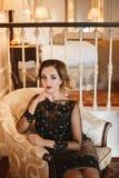 A mulher de neg?cios nova e 'sexy' em um vestido de cocktail ? moda senta-se em uma poltrona do vintage no interior luxuoso imagem de stock