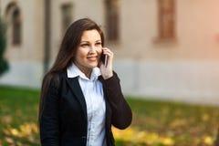 Mulher de neg?cios ou empres?rio bem sucedido que falam no telefone celular ao andar exterior Funcionamento da mulher de neg?cio  fotos de stock royalty free