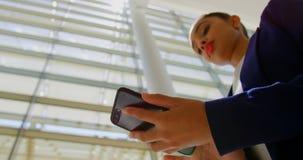 Mulher de neg?cios que usa o telefone celular no escrit?rio 4k vídeos de arquivo