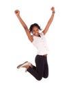 Mulher de negócio americana africana nova que salta, conceito do sucesso Fotografia de Stock