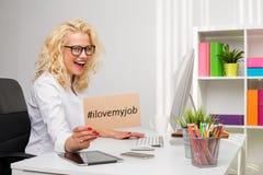 Mulher de negócio na exibição do escritório eu amo meu cartão do trabalho Fotos de Stock Royalty Free