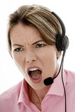 Mulher de negócio nova atrativa irritada que usa uns auriculares do telefone Imagem de Stock
