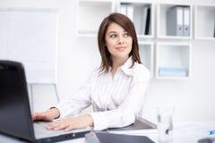 Mulher de negócio nova que senta-se na mesa no escritório Fotografia de Stock
