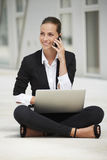 Mulher de negócio nova que senta-se no pavimento usando o portátil ao falar no telefone Fotografia de Stock Royalty Free