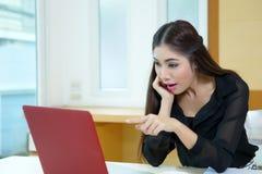 A mulher de negócio nova surpreendeu apontar à tela do portátil Fotos de Stock