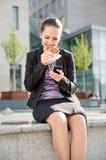 Mulher de negócio que come e que trabalha com telefone Imagens de Stock