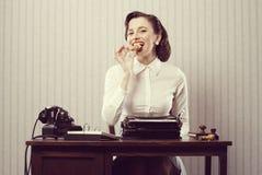 Mulher de negócio que come uma cookie Fotografia de Stock Royalty Free
