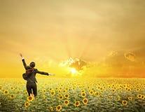 A mulher de negócio que salta no por do sol sobre girassóis coloca Fotografia de Stock Royalty Free