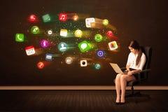Mulher de negócio que senta-se na cadeira do escritório com portátil e colorida Fotografia de Stock Royalty Free
