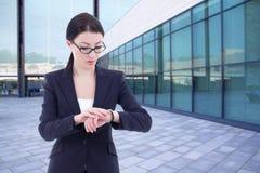 A mulher de negócio verifica o tempo em seu relógio de pulso que está na rua Fotografia de Stock Royalty Free