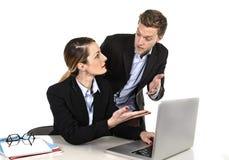 Mulher de negócios atrativa nova que trabalha no portátil do computador no escritório que discute com o colega do trabalho no esf Fotografia de Stock Royalty Free