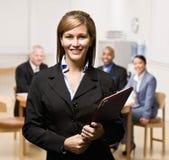 Mulher de negócios com caderno e colegas de trabalho Fotografia de Stock Royalty Free