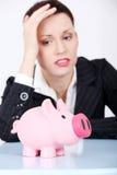 Mulher de negócios deprimida que olha seu banco piggy. Fotos de Stock Royalty Free