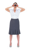 Mulher de negócios elegante Unsmiling que olha através dos binóculos Foto de Stock Royalty Free
