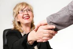 Mulher de negócios envelhecida meio de sorriso, agitando as mãos Imagem de Stock