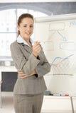 Mulher de negócios nova que apresenta no sorriso do escritório Fotografia de Stock Royalty Free
