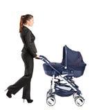 Mulher de negócios nova que empurra um carrinho de criança de bebê Imagem de Stock Royalty Free