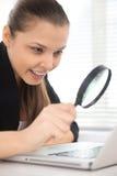 Mulher de negócios observando o portátil com lupa Fotografia de Stock Royalty Free
