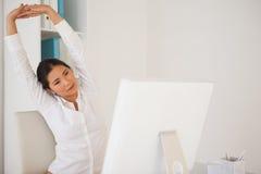 Mulher de negócios ocasional que estica em sua mesa Fotografia de Stock Royalty Free
