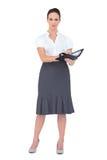 Mulher de negócios séria que guarda seu datebook Fotografia de Stock