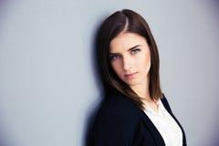 Mulher de negócios séria que inclina-se na parede cinzenta Imagens de Stock Royalty Free
