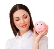 Mulher de negócios séria que olha um piggybank Fotografia de Stock
